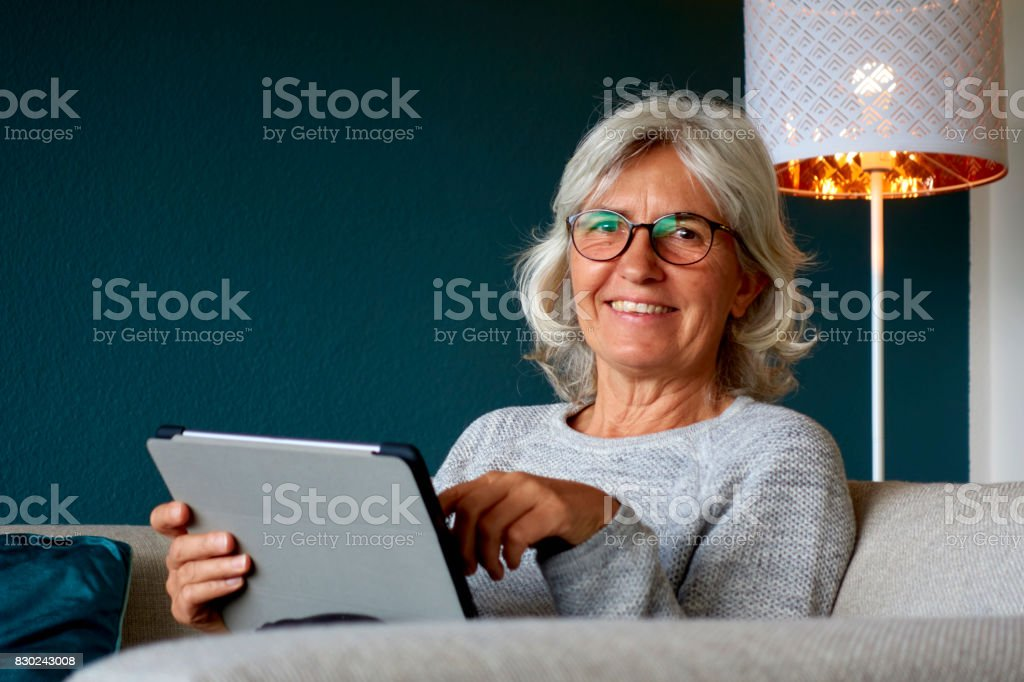 Senior Woman relaxing on the Couch at Home surfing on the Internet with a Tablet stock photo