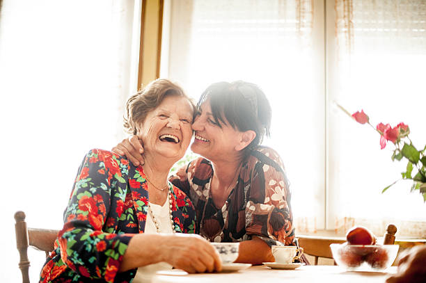 senior woman relaxing with her daughter at home - daughter stock photos and pictures
