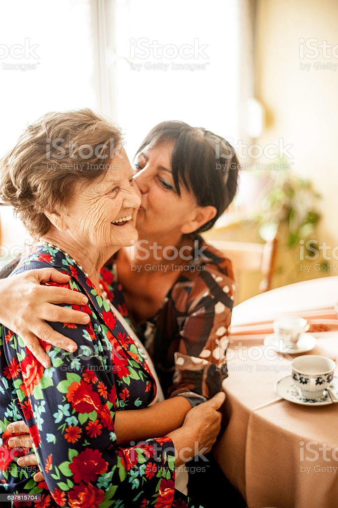Senior Woman Relaxing with her Daughter at Home stock photo