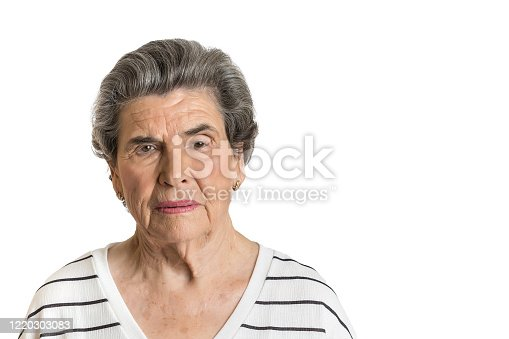 Portrait of elderly lady in casual shirt looking seriously at camera isolated on white background