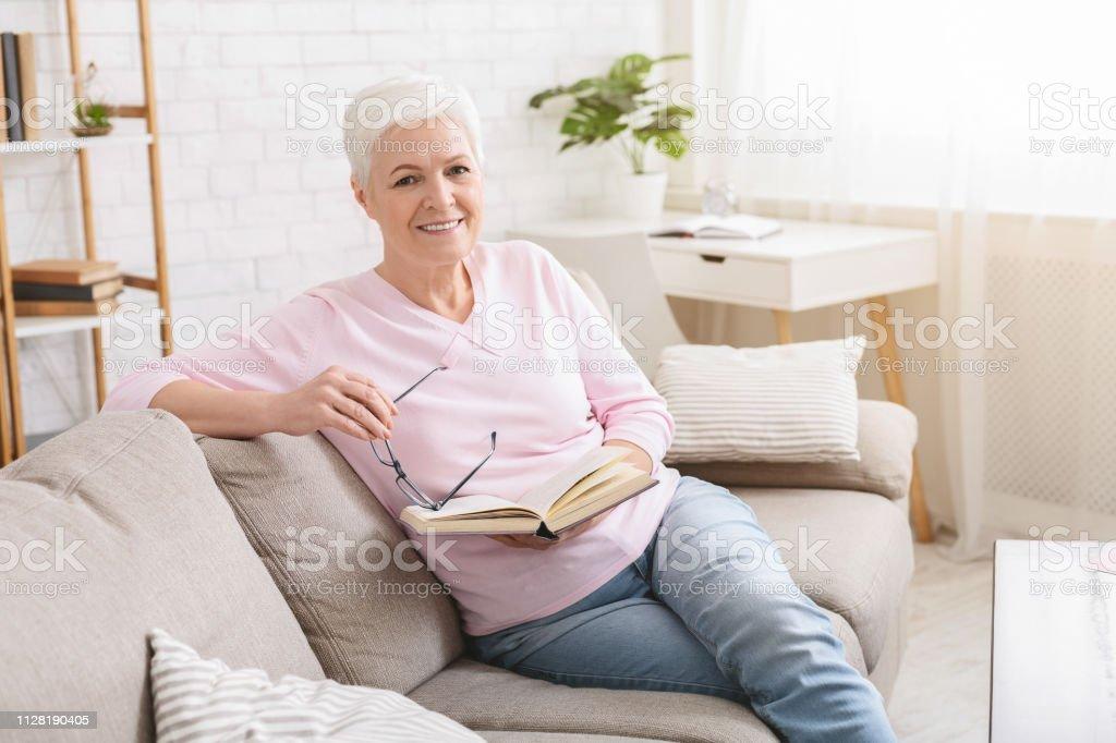 Ältere Frau ruht auf Sofa und Buch – Foto