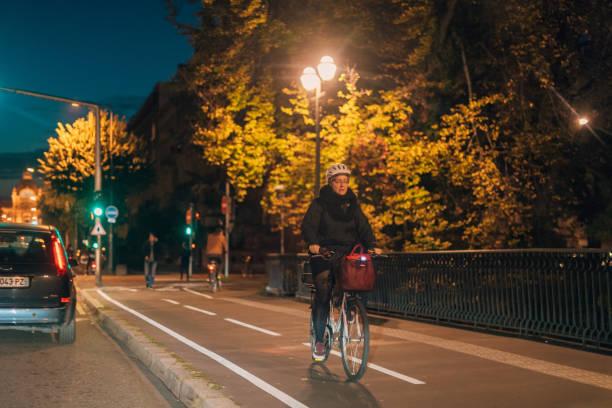 senior woman riding a bike at night in central strasbourg - motociclista стоковые фото и изображения
