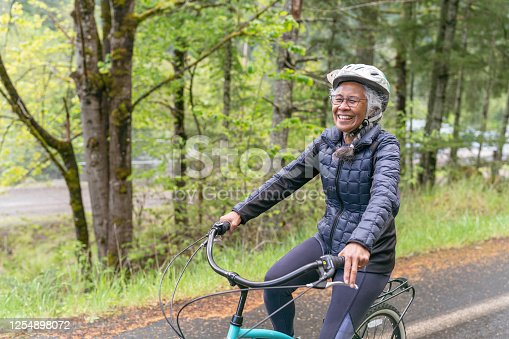 An ethnic senior woman rides her bicycle along a country road in the forest. The road is sloping downhill as she rides toward the camera.