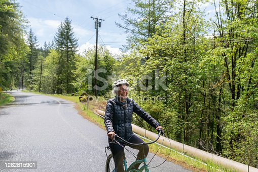 An ethnic senior woman rides her bicycle along a rural road in the woods that is sloping downhill.