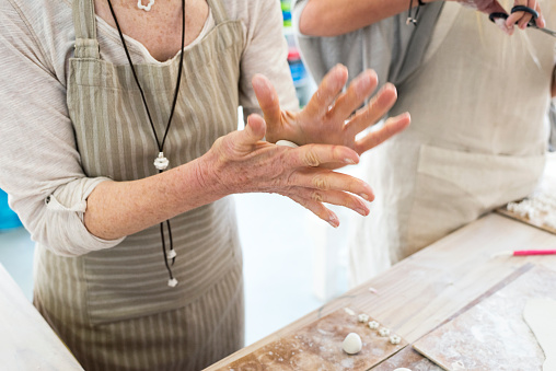 Senior woman rolling clay