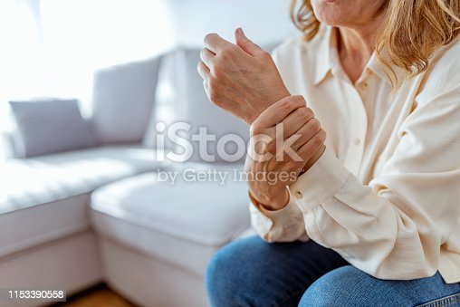 Photo of Elderly lady is enduring strong ache while sitting on the sofa during the day. Senior Woman At Home Suffering With Arthritis. Upset stressed mature middle-aged woman feeling pain ache.