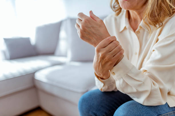 senior woman rubbing her wrist and arm suffering from rheumatism - infiammazione foto e immagini stock