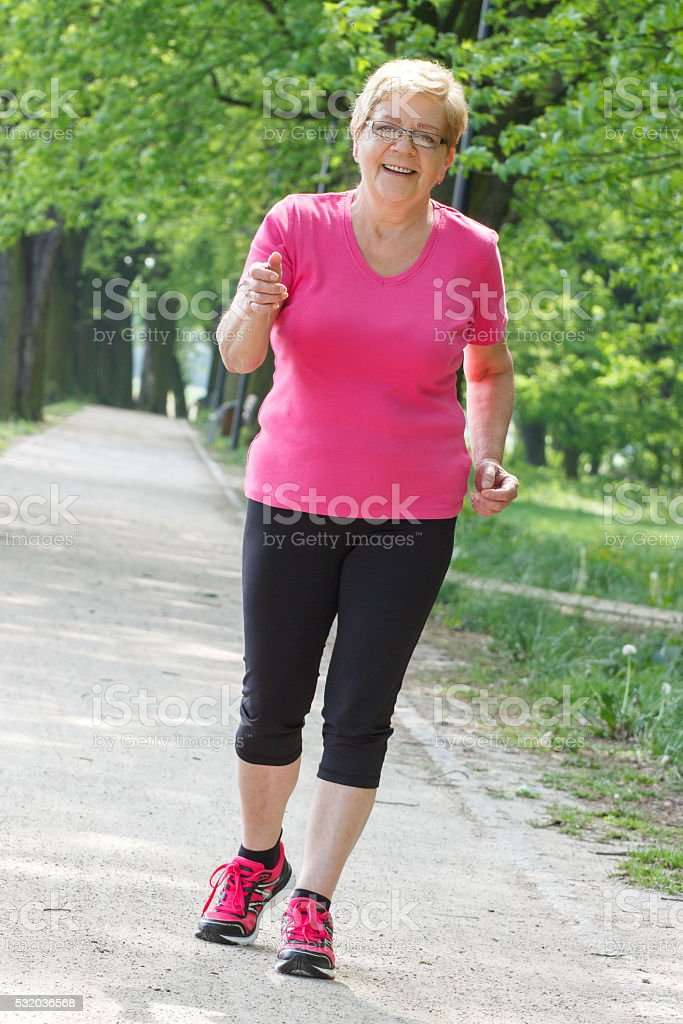Senior woman running in sunny park, jogging outside, healthy lifestyle stock photo