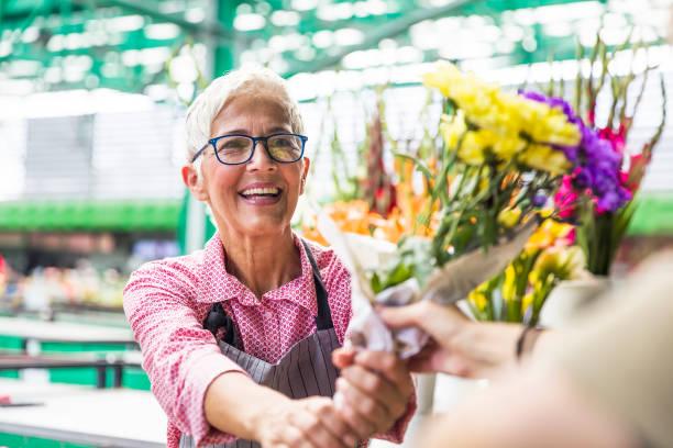 로컬 꽃 시장에 고위 여자 판매 꽃 - 시장 소매점 뉴스 사진 이미지