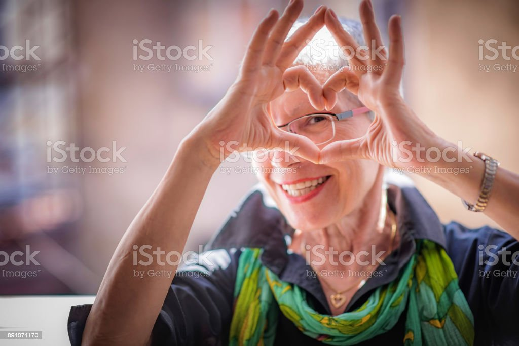 Senior woman sending love stock photo