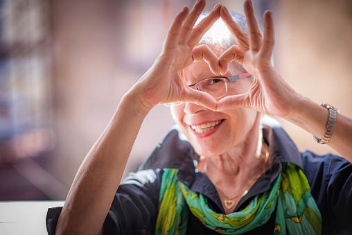 Senior Woman Sending Love - zdjęcia stockowe i więcej obrazów Człowiek dojrzały