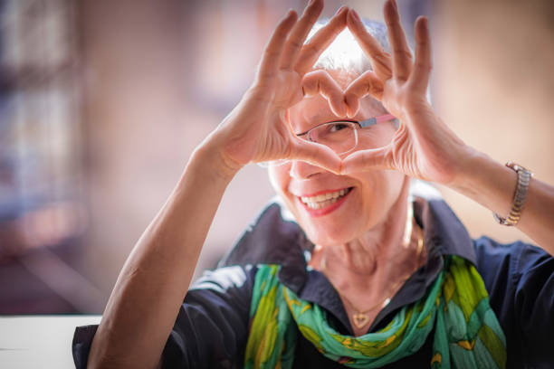 senior woman sending love - geriatrics stock pictures, royalty-free photos & images