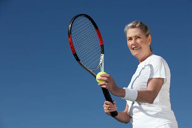 Senior femme servant une balle de tennis - Photo