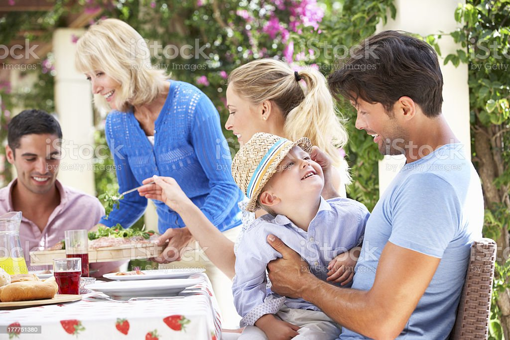 Senior Woman Serving At Multi Generation Family Meal royalty-free stock photo