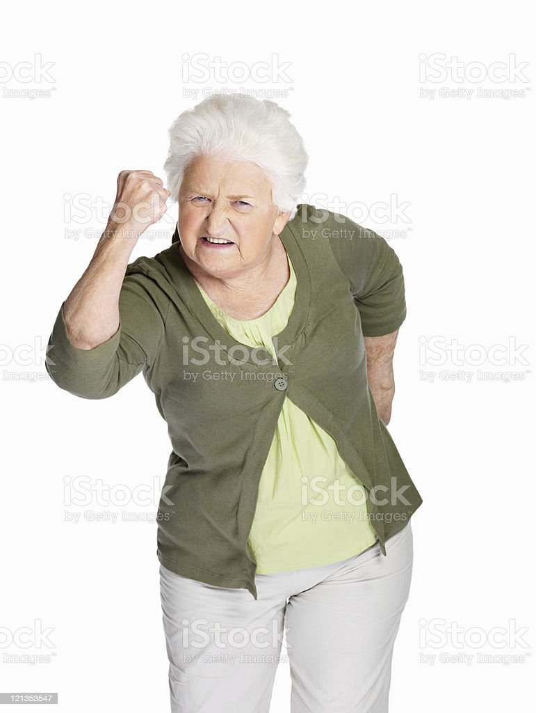 Senior woman shakes her fist at you stock photo