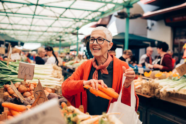 Senior woman shopping at the vegetable marketplace stock photo
