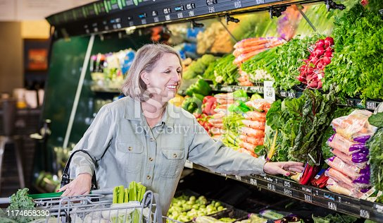 A senior woman in her 60s in a supermarket, shopping in the produce aisle, looking at the vegetables as she pushes her shopping cart.