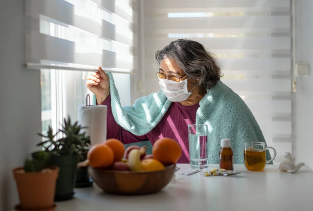 Senior woman sick with Covid-19 wearing a medical mask staying at home under quarantine stock photo