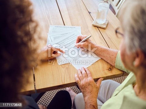 istock Senior Woman Signing Documents in Her Home 1171173643