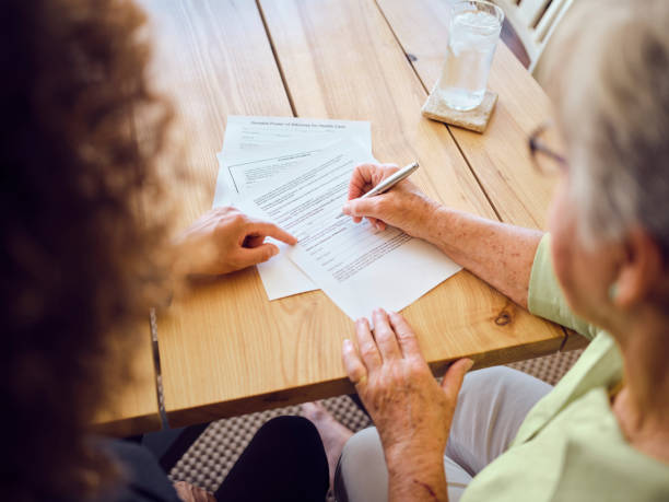 Senior Woman Signing Documents in Her Home stock photo