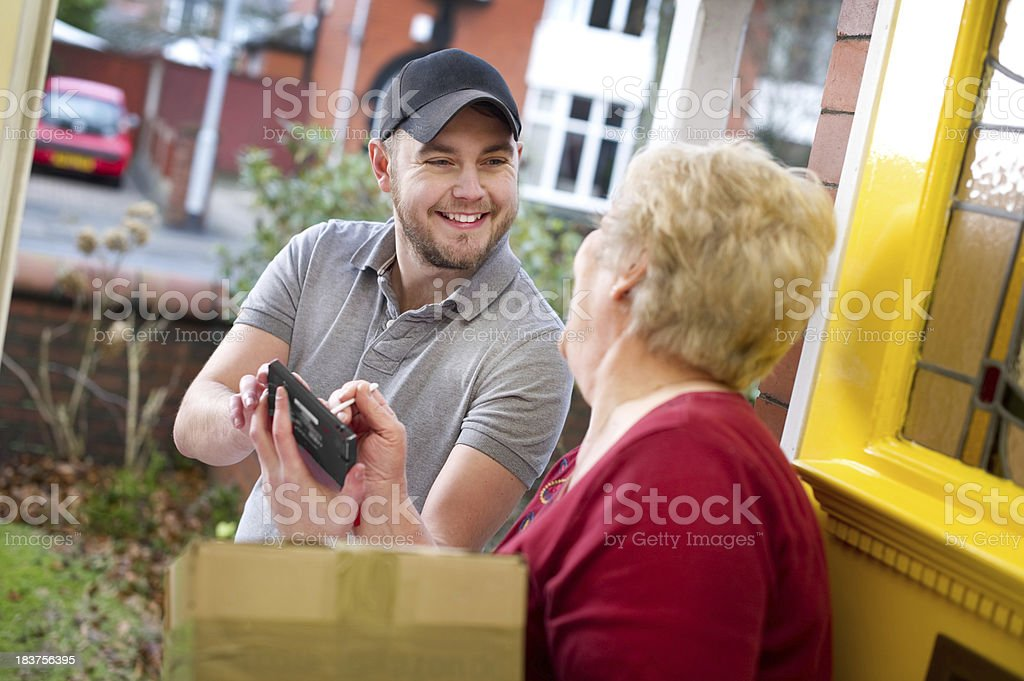 Senior woman signing for her package royalty-free stock photo