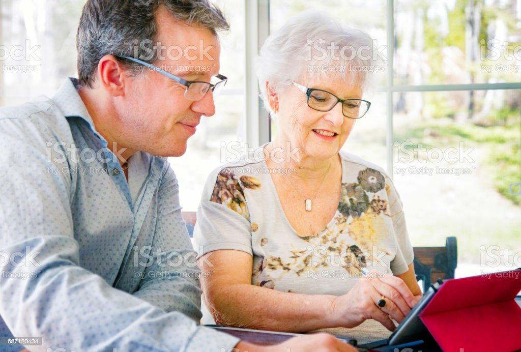 Documento de sinais mulher sênior na tablet com homem satisfeito ao seu lado. - foto de acervo
