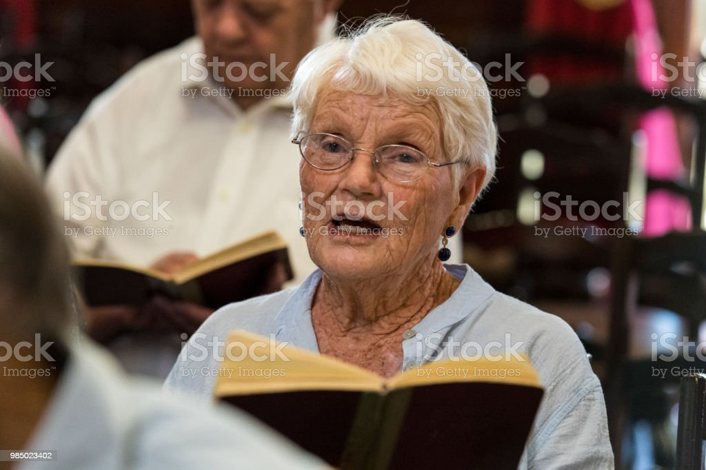 Senior woman singing in church stock photo