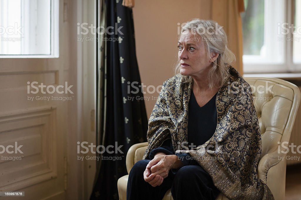 senior woman sits alone in living room and looks sad stock photo