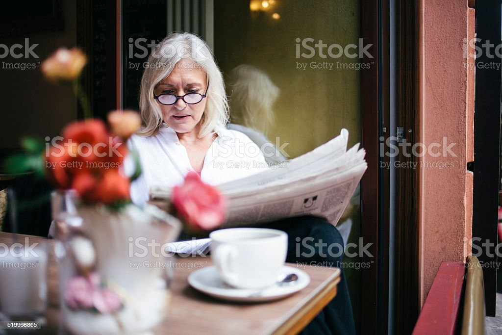 senior woman sits in a Sidewalk Cafe and reads newspaper stock photo