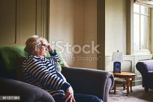 Thoughtful senior woman sitting alone on couch at home