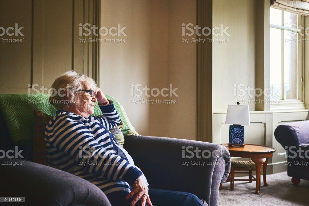 Ältere Frau, die allein zu Hause sitzen – Foto