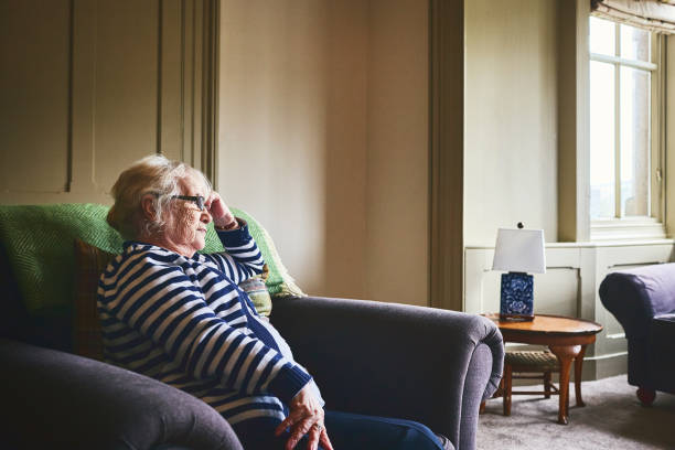Senior woman sitting alone at home stock photo