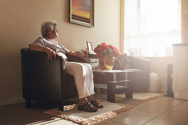 senior woman sitting alone on a chair at home - 寂しさ ストックフォトと画像