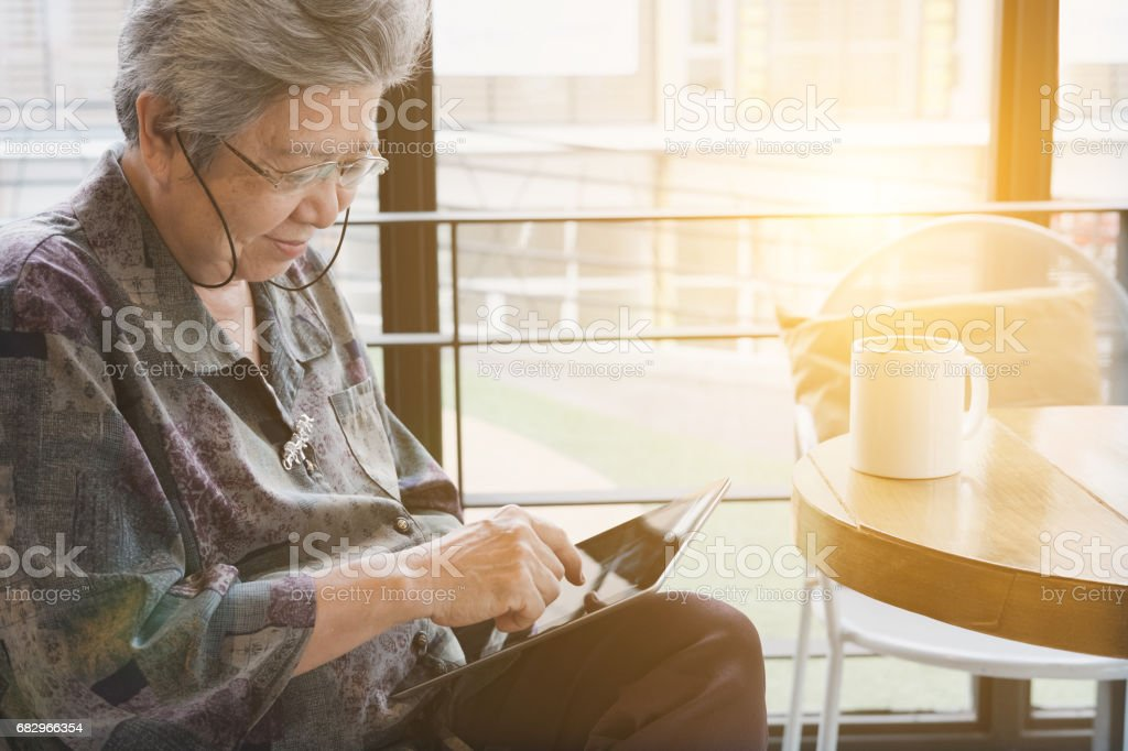 Senior woman sitting and resting in cafe coffee shop using digital tablet computer. social networking concept royalty-free stock photo