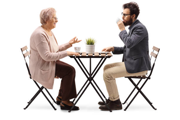 Senior woman sitting at a table with coffee and talking to a young bearded man stock photo