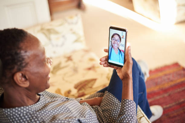 Senior woman sitting at home and talking with her doctor on her smart phone stock photo