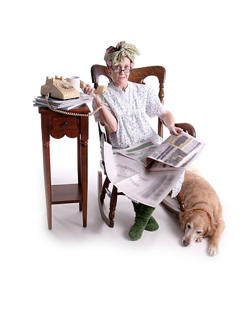 Senior mujer sentada junto a perro leyendo el periódico - foto de stock