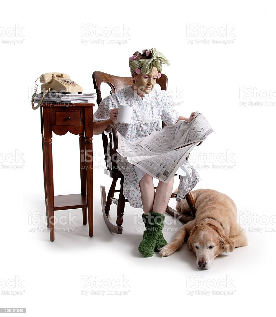 Senior Woman Sitting Beside Dog and Reading Newspaper royalty-free stock photo