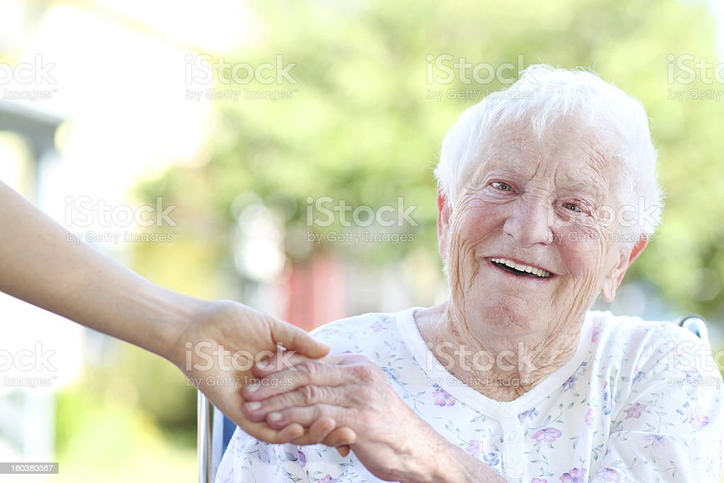 Senior woman sitting down holding the hand of her carer royalty-free stock photo