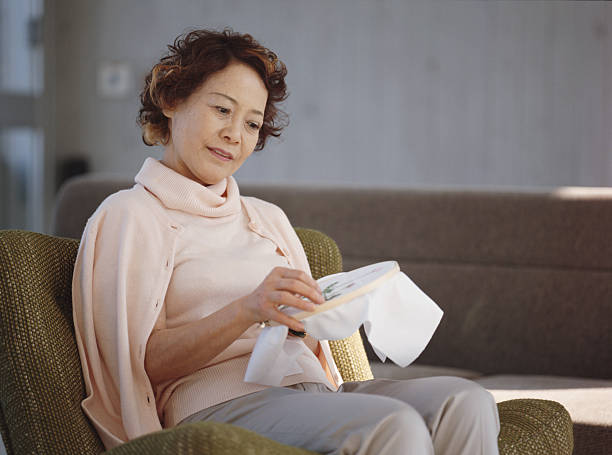 Senior woman sitting in armchair embroidering stock photo