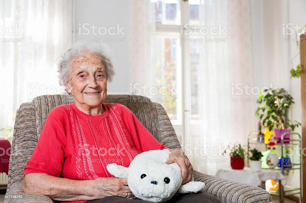 Senior woman sitting in armchair stock photo