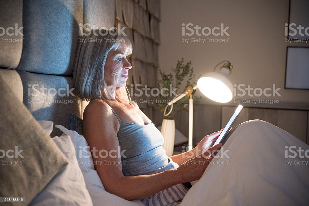Senior woman sitting in bed at night with tablet stock photo