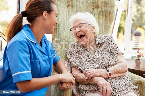 istock Senior Woman Sitting In Chair And Laughing With Nurse In Retirement Home 1047536650