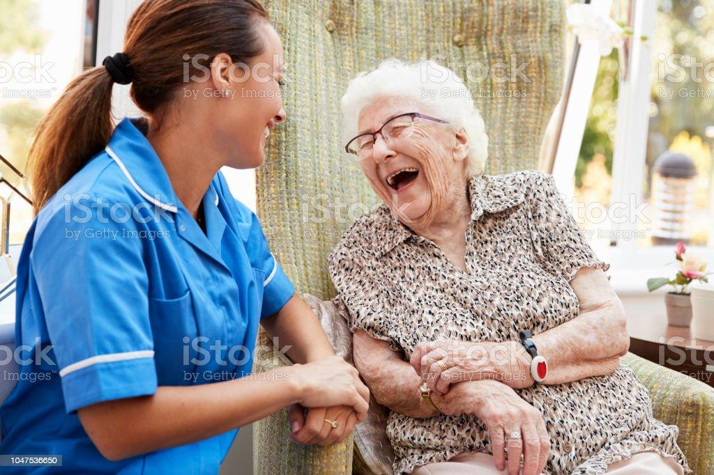 Ältere Frau sitzt im Stuhl und lachen mit Krankenschwester im Altenheim – Foto