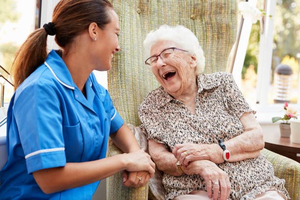 senior woman sitting in chair and laughing with nurse in retirement home - geriatrics stock pictures, royalty-free photos & images