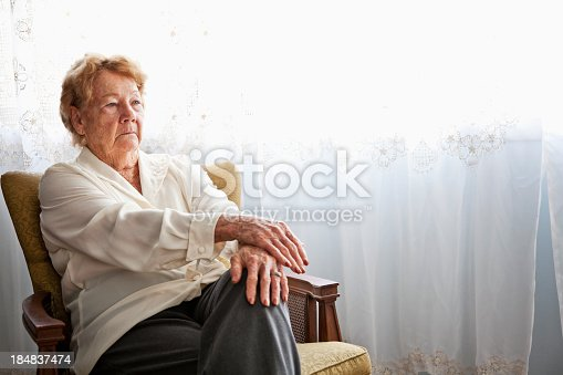 Senior woman (80s) at home sitting in chair by window.