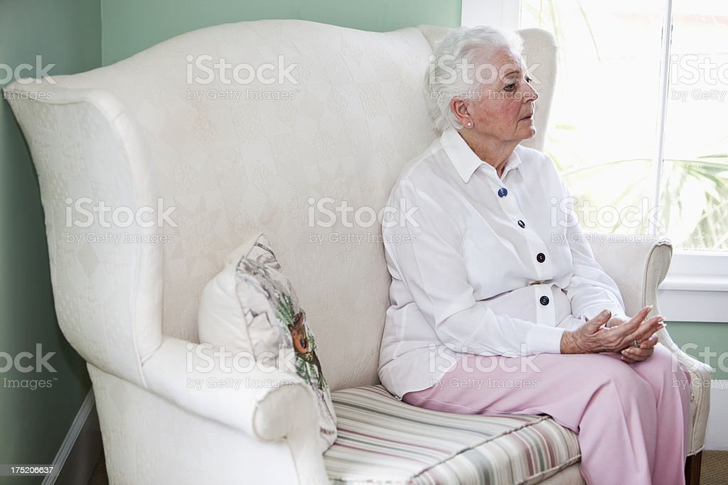 Senior woman sitting in chair by window royalty-free stock photo