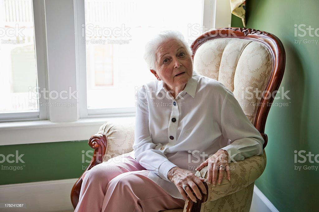 Senior woman sitting in chair by window stock photo