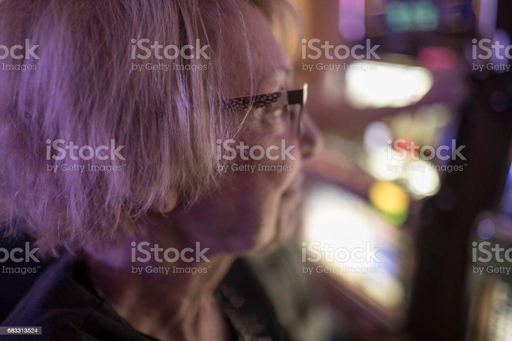 Een senior vrouw, zit een gokautomaat, is gelukkig het controleren van het scherm terwijl het gokken in een casino van Las Vegas. royalty free stockfoto