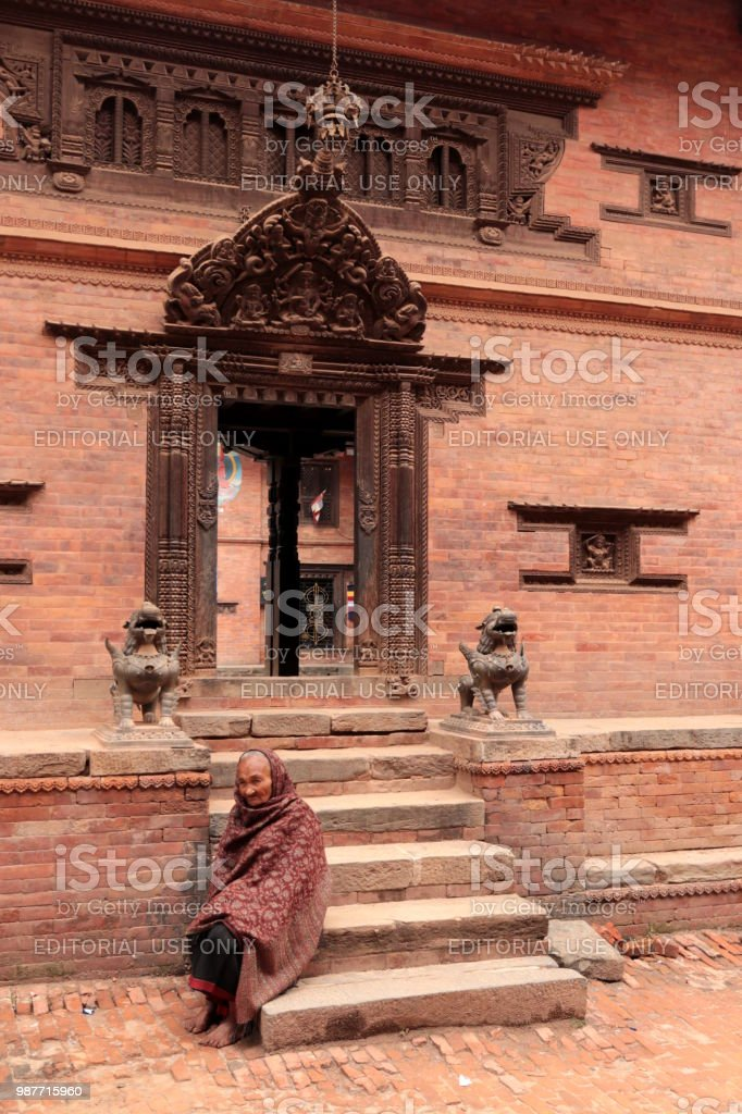 Senior woman sitting in front of a tample in Bakhtapur durbar square, Nepal stock photo